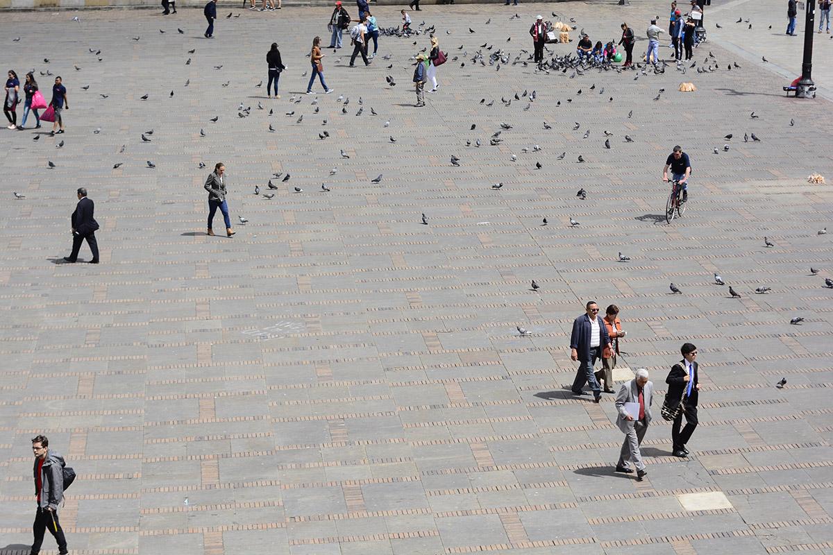 Decenas de personas y de palomas dispersas por una plaza